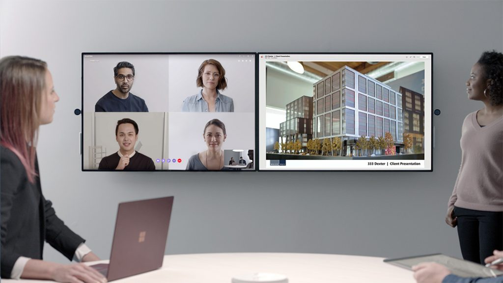 Two people in an office with Surface Hub 2 and Surface Laptop